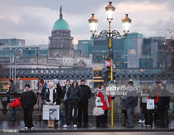 Commuters wait at a bus stop in the early morning light in Dublin Ireland on November 22 2010 Anger mounted in Ireland Monday after Prime Minister...