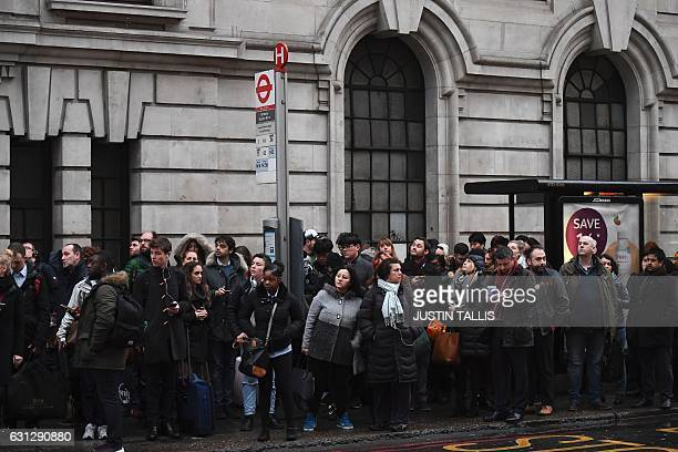 Commuters wait at a bus stop near to Victoria station in central London on January 9 2017 as industrial action halted the vast majority of services...
