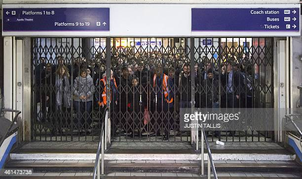 Commuters wait behind barriers to ender the underground at Victoria rail station during a one day strike by bus drivers in London on Janurary 13 2015...