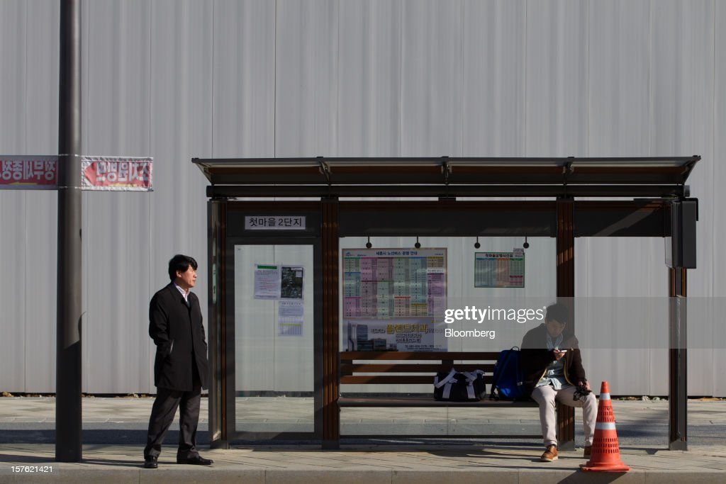Commuters wait for a bus at a bus stop in Sejong, South Korea, on Tuesday, Dec. 4, 2012. The construction of Sejong City 120 kilometers (75 miles) south of the capital fulfills the vision of the late President Roh Moo Hyun, who pledged to reduce the dominance of Seoul and pump money into a region courted for its swing voters. Photographer: SeongJoon Cho/Bloomberg via Getty Images