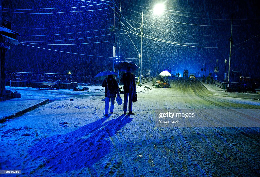 Commuters wait for a passenger bus during heavy snowfall on January 17, 2013 in Srinagar, Indian Administered Kashmir, India. Several parts of the Kashmir Valley, including the summer capital Srinagar, experienced fresh snowfall today, prompting the authorities to issue an avalanche warning and leading to closure of the Jammu-Srinagar Highway, the only road link between Kashmir and rest of India.