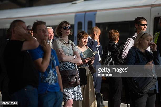 Commuters wait for a train operated by GoAhead Group Plc's SouthEastern railway franchise on a newly opened platform at London Bridge railway station...