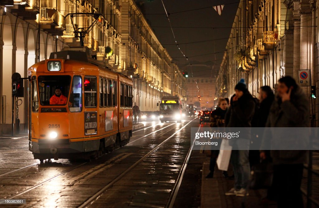 Commuters wait for a tram at a tram stop at night in Turin, Italy, on Tuesday, Jan. 29, 2013. Italy sold 8.5 billion euros ($11.4 billion) of six-month Treasury bills as rates dropped to the lowest in almost three years as the European Central Bank's pledge to buy bonds continues to provide an effective backstop even amid rising political concerns. Photographer: Alessia Pierdomenico/Bloomberg via Getty Images