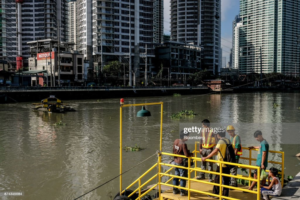Commuters wait for the boat to cross the Pasig River as medium and high-rise real estate stands in the background in Mandaluyong, Metro Manila, Philippines, on Tuesday, Nov. 14, 2017. Economists are forecasting the Philippines to be among the first to raise interest rates in the region and the International Monetary Fund saidlast week the central bank should be ready to tighten if there are signs of overheating. Photographer: Veejay Villafranca/Bloomberg via Getty Images