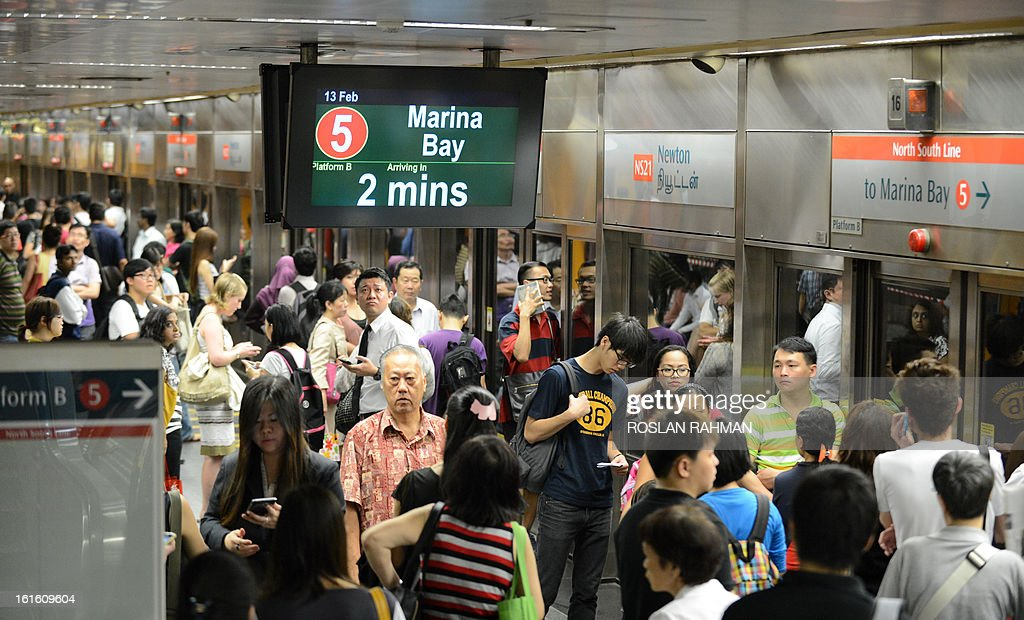Commuters wait for the train at the subway staion in Singapore on February 13, 2013. Singapore on February 4 defended its population policies after an outcry over a forecast that it could have 30 percent more people in less than 20 years, with foreigners forming almost half the total.