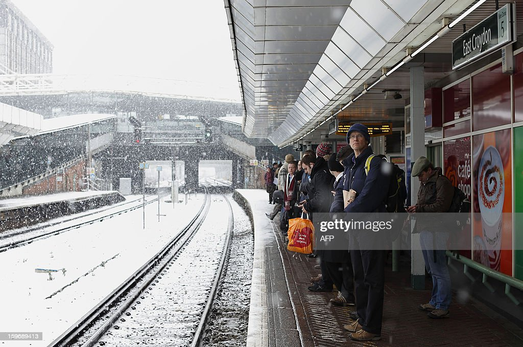 Commuters wait for trains during falling snow at East Croydon train station, south of London, on January 18, 2013. Snow swept across Britain on Friday, forcing airports to cancel dozens of flights and more than 2,000 schools to close.