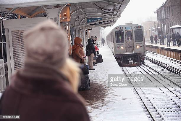 Commuters wait on a snowcovered platform for an L train in the Wicker Park neighborhood on February 5 2014 in Chicago Illinois About six inches of...