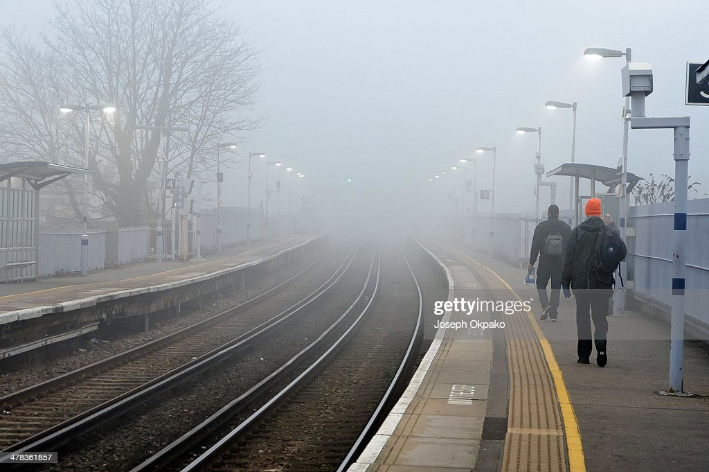 Commuters wait on platform in the thick fog for the Overground train to arrive on March 13, 2014 in London, England. Thick fog hit much of England and Wales this morning, causing travel disruptions and flight cancellations.