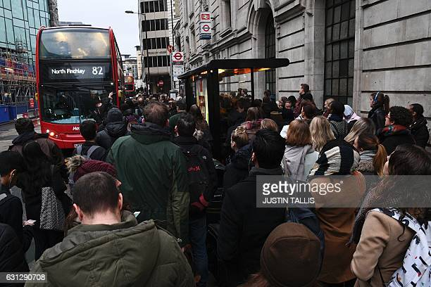 Commuters wait to board a bus at a bus stop near to Victoria station in central London on January 9 2017 as industrial action halted the vast...