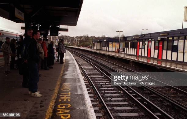 Commuters waiting on a platform at Dartford Railway Station London Mick Jagger and Keith Richards the founder members of the band the Rolling Stones...