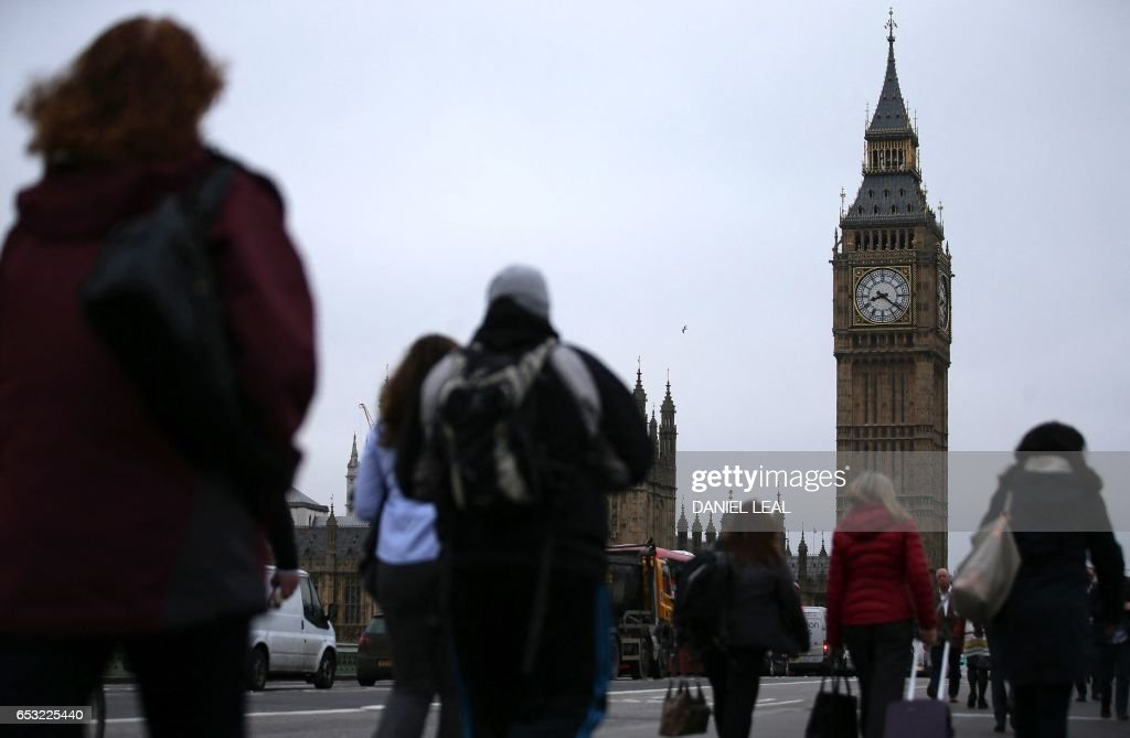 Commuters walk accross Westminster Bridge, backdropped by The Elizabeth Tower, better known as 'Big Ben', and the Houses of Parliament in central London on March 14, 2017. Prime Minister Theresa May is set to begin the countdown to Brexit after parliament gave her the green light -- and Scotland wrong-footed her by launching a fresh bid for independence. Downing Street has played down speculation that May could announce Tuesday that she is triggering the Article 50 process to leave the European Union, indicating that it would take place later in the month. / AFP PHOTO / Daniel LEAL