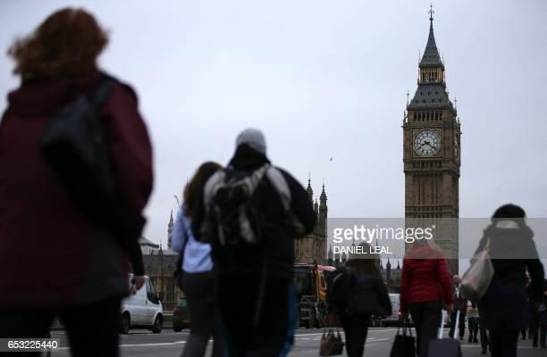Commuters walk accross Westminster Bridge backdropped by The Elizabeth Tower better known as 'Big Ben' and the Houses of Parliament in central London...