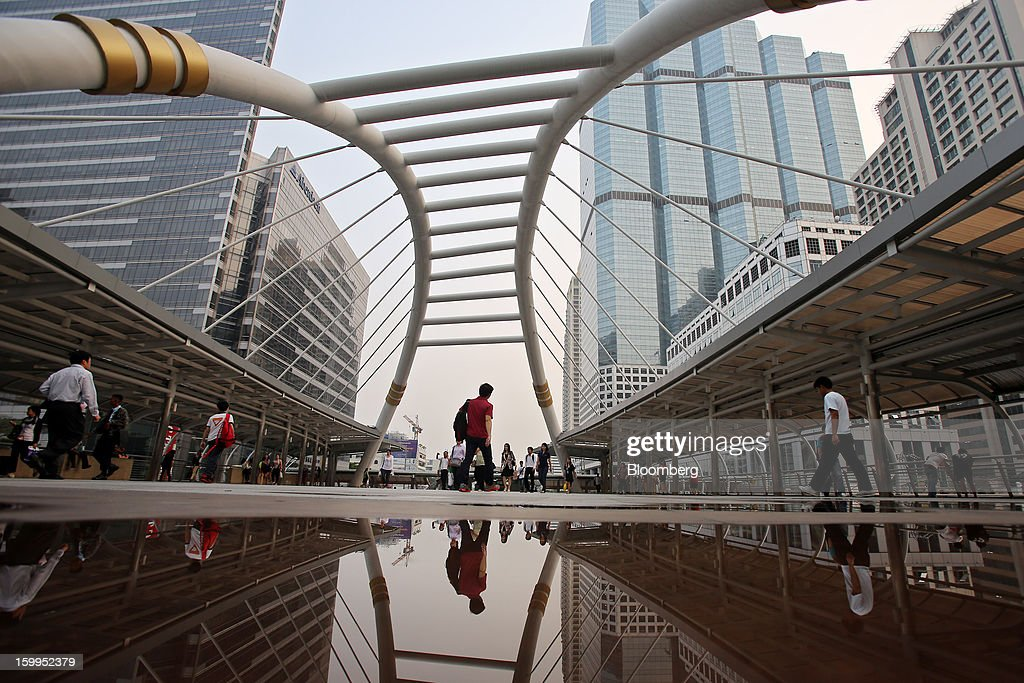 Commuters walk across a pedestrian bridge in the Sathorn district of Bangkok, Thailand, on Wednesday, Jan. 23, 2013. Prime Minister Yingluck Shinawatra's government last month approved a new round of increases in the daily minimum wage to 300 baht ($9.8) from the beginning of this year, after a similar raise in April in seven provinces including Bangkok. Photographer: Dario Pignatelli/Bloomberg via Getty Images
