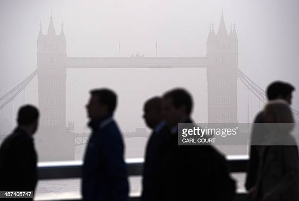Commuters walk across London Bridge in the early morning fog in central London on April 30 as a strike by underground train staff affected a second...