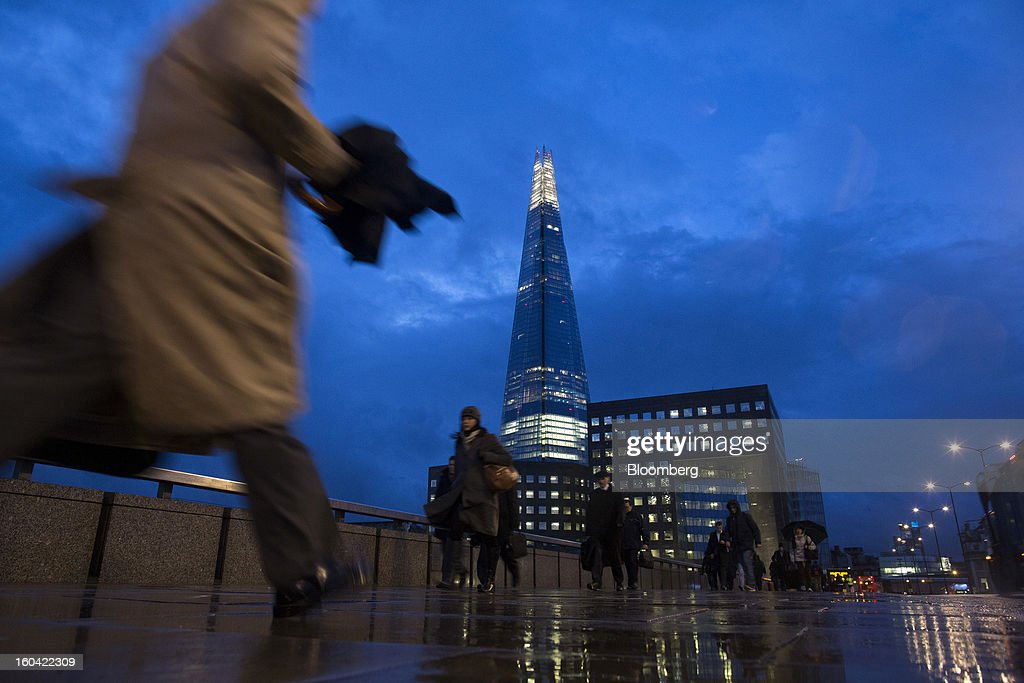 Commuters walk across London Bridge near the Shard tower, center, at dawn in London, U.K., on Thursday, Jan. 31, 2013. The Shard, which stands at 309.6 meters on London's South Bank, opens to the public on Feb. 1, and is owned by LBQ Ltd., which brings together the State of Qatar (the majority shareholder) and Sellar Property Group Ltd., with non-equity funding by Qatar National Bank. Photographer: Simon Dawson/Bloomberg via Getty Images