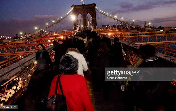 Commuters walk across the Brooklyn Bridge during the evening rush hour December 21 2005 in New York Transport Workers Union President Roger Toussaint...