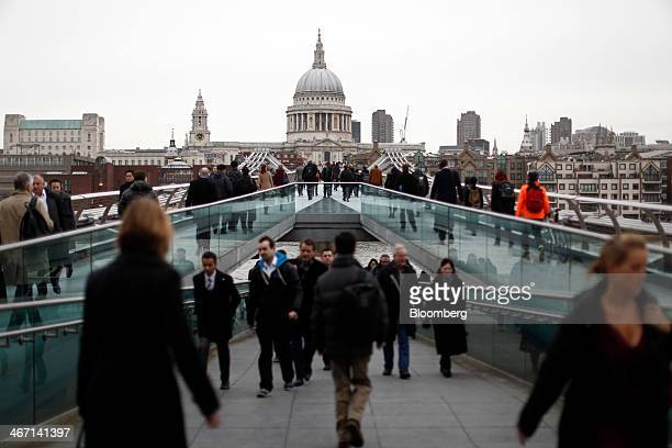 Commuters walk across the Millennium Bridge towards St Paul's Cathedral and the City of London in the morning rush hour in London UK on Thursday Feb...