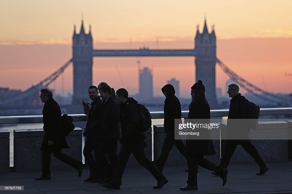 Commuters walk across the River Thames on London Bridge, past Tower Bridge, in London, U.K., on Friday, Nov. 30, 2012. U.K. banks have become more unwilling to finance development projects without a tenant committed to lease space or a buyer for the completed property. Photographer: Chris Ratcliffe/Bloomberg via Getty Images