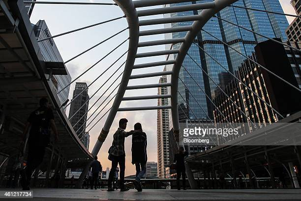 Commuters walk along a pedestrian bridge in the Sathorn financial district in Bangkok Thailand on Friday Jan 9 2015 Thailands former Prime Minister...
