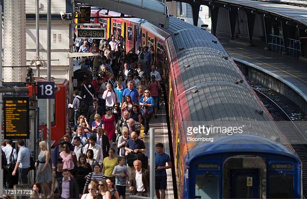 Commuters walk along a platform after exiting a passenger train operated by South West Trains Ltd at Waterloo rail station in London UK on Tuesday...