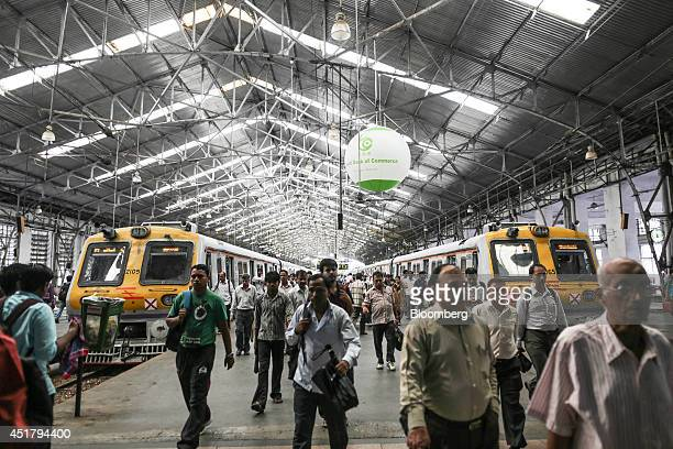 Commuters walk along a railway platform at Churchgate Station in Mumbai India on Friday July 4 2014 Indian Railways' annual budget is scheduled to be...