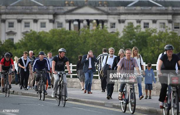 Commuters walk and cycle over Waterloo Bridge as the evening rush hour begins early on July 8 2015 in London England London Underground workers are...