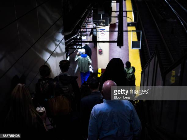 Commuters walk down the stairs to a Long Island Railroad Co train platform inside Pennsylvania Station in New York US on Friday May 26 2017...