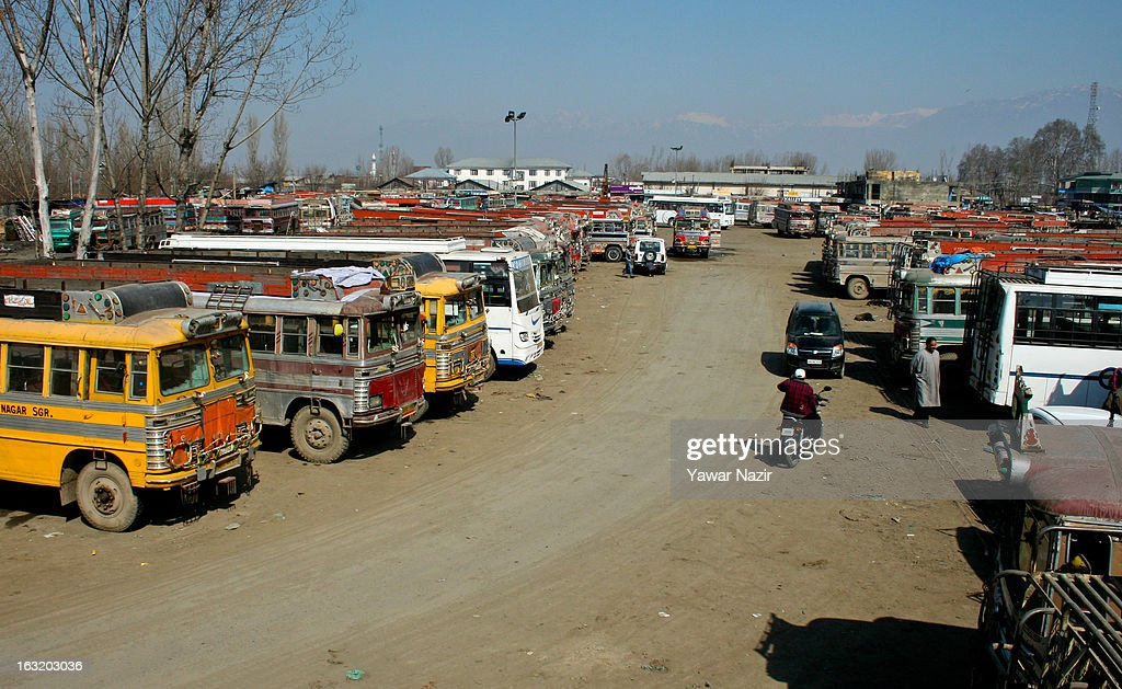 Commuters walk in a bus stand next to the stranded buses during a curfew like restriction on March 06, 2013 in Srinagar, the summer capital of Indian Administered Kashmir, India. Indian authorities imposed curfew like restrictions in most parts of Kashmir following a killing of kashmiri youth by Indian army in North Kashmir's Baramulla district yesterday.