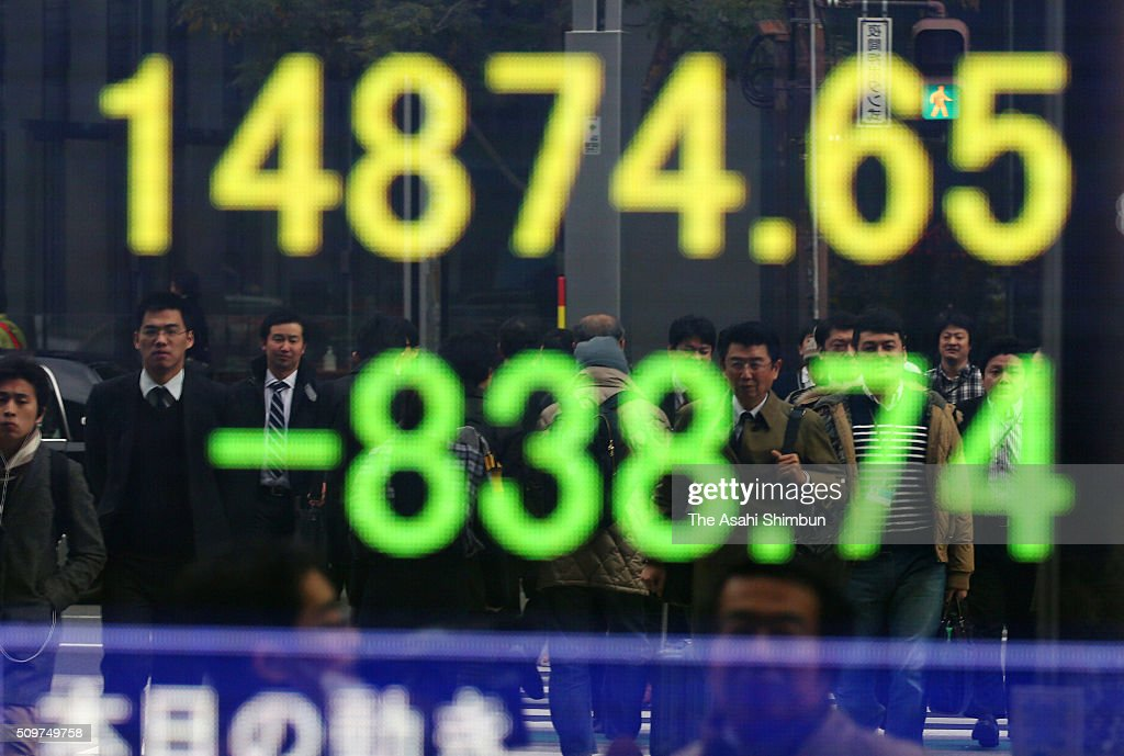 Commuters walk in front of an electric board displaying the Nikkei index on February 12, 2016 in Tokyo, Japan. Japan's Nikkei 225 index continues to drop, below 15,000 points, first time in 16 month amid the Japanese Yen soaring and uncertainty of the global economy.