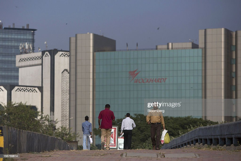 Commuters walk in front of the Wockhardt Ltd. headquarters in the Bandra Kurla Complex in Mumbai, India, on Tuesday, Nov. 6, 2012. Reserve Bank of India Governor Duvvuri Subbarao lowered the RBI's forecast for India's gross domestic product growth in the year through March to 5.8 percent, the slowest in almost a decade, from 6.5 percent. Photographer: Brent Lewin/Bloomberg via Getty Images