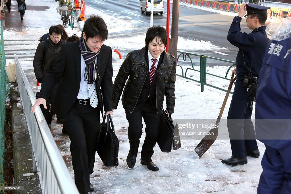 Commuters walk on a flozen road, a day after the snowfall on January 15, 2013 in Tokyo, Japan. A strong low pressure system caused heavy snow and strong wind in the coast area including Tokyo, more than 500 injured.
