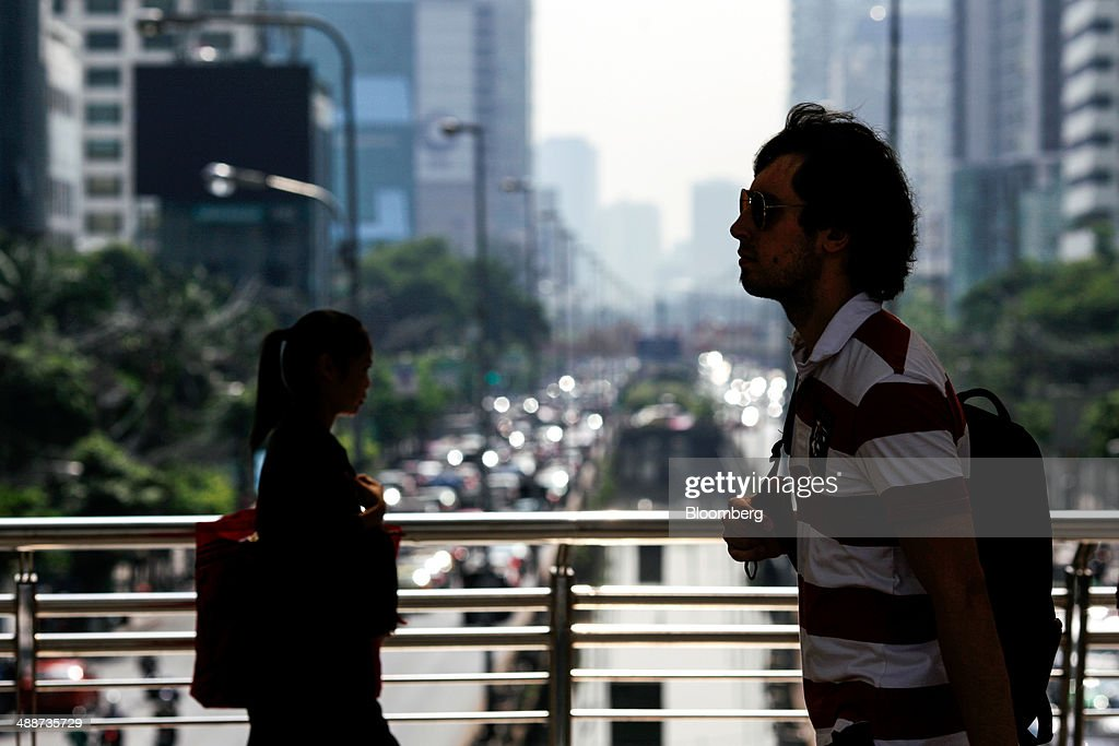 Commuters walk on a pedestrian bridge in the Sathorn financial district in Bangkok, Thailand, on Thursday, May 8, 2014. The baht fell to a one-month low and stocks slumped on concern global investors will shun Thailand after a court ruling to remove Yingluck Shinawatra as prime minister worsened the nation's political crisis. Photographer: Dario Pignatelli/Bloomberg via Getty Images