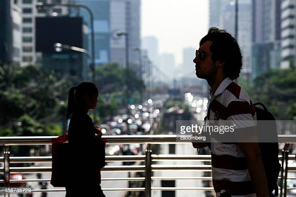 Commuters walk on a pedestrian bridge in the Sathorn financial district in Bangkok Thailand on Thursday May 8 2014 The baht fell to a onemonth low...