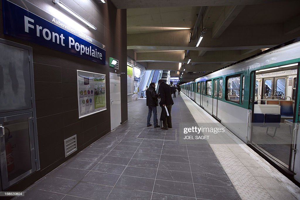 Commuters walk on a platform of the Front Populaire subway station on its inauguration day on December 18, 2012 in Aubervilliers-Saint-Denis, north of Paris.