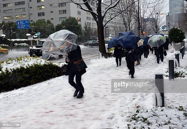 Commuters walk on a snow covered road in Tokyo on January 18 2016 Heavy snow blanketed Tokyo metropolitan area and transportation systems were...