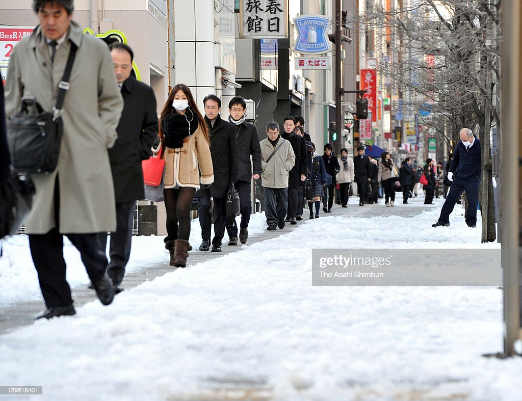 Commuters walk on a track to avoid the flozen road, a day after the snowfall on January 15, 2013 in Tokyo, Japan. A strong low pressure system caused heavy snow and strong wind in the coast area including Tokyo, more than 500 injured.
