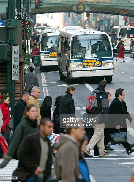 Commuters walk pass MTA buses on 42nd Street as New Yorkers prepare 16 December 2002 for a possible transit strike between the transit union and the...