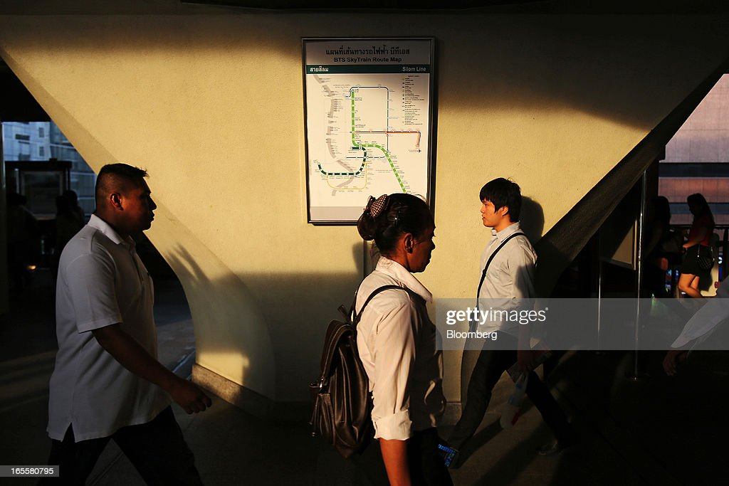 Commuters walk past a route map for the Bangkok Mass Transit System Pcl SkyTrain, a unit of BTS Group Holdings Pcl, at the Chong Nonsi Station in Bangkok, Thailand, on Thursday, April 4, 2013. The BTS Rail Mass Transit Growth Infrastructure Fund, backed by Bangkok's SkyTrain, raised about 62.5 billion baht ($2.1 billion) in Thailand's biggest initial public offering. Photographer: Dario Pignatelli/Bloomberg via Getty Images