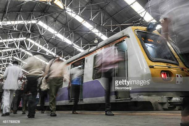 Commuters walk past a train as it sits on a platform at Churchgate Station in Mumbai India on Friday July 4 2014 Indian Railways' annual budget is...