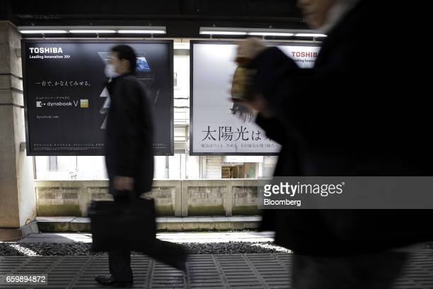 Commuters walk past advertisements for Toshiba Corp's products displayed at a train station in Tokyo Japan on Tuesday March 28 2017 Toshiba...