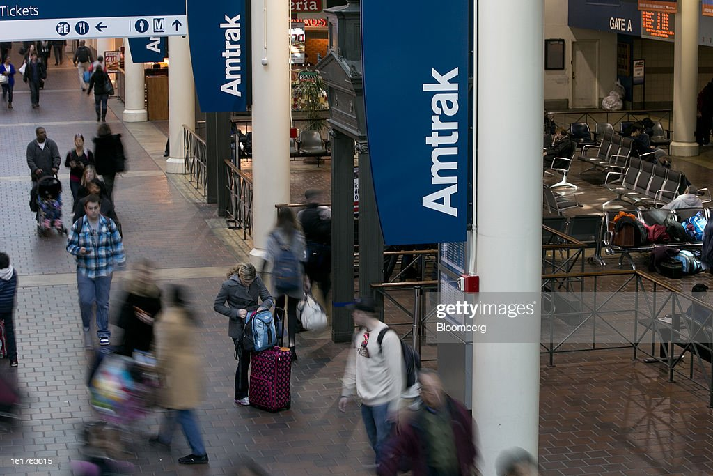 Commuters walk past Amtrak signs at Union Station in Washington, D.C., U.S., on Friday, Feb. 15, 2013. Amtrak, the U.S. long-distance passenger railroad and federally subsidized since its beginning 41 years ago, last month reported its lowest operating loss in nearly four decades, announcing the passenger rail company had reduced its total operating loss by 19 percent compared to the previous year. Photographer: Andrew Harrer/Bloomberg via Getty Images