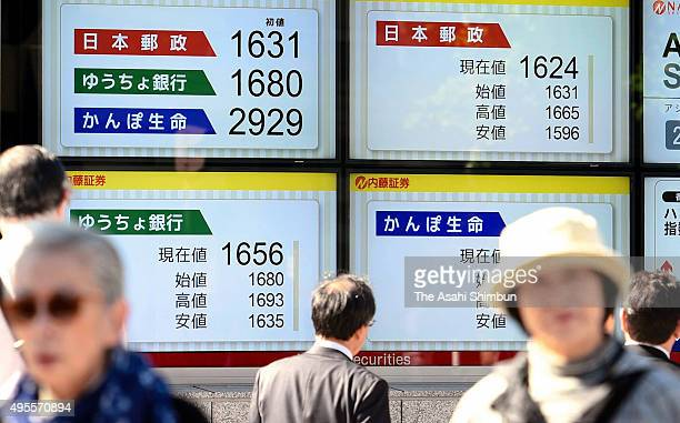 Commuters walk past an electric board displaying newly debuted Japan Post companies share price on November 4 2015 in Tokyo Japan The three companies...