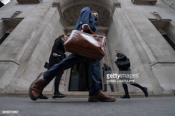 TOPSHOT Commuters walk past an entrance to the Lloyds building in central London on March 29 2017 British Prime Minister Theresa May will formally...