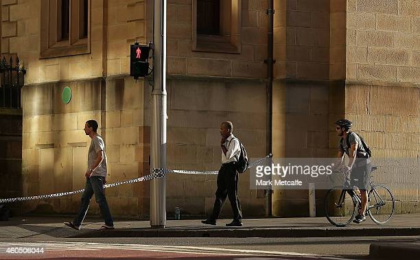 Commuters walk past police tape on St James Rd on their way to work on December 16 2014 in Sydney Australia The siege in Sydney's Lindt Cafe in...