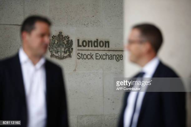 Commuters walk past the London Stock Exchange in the City of London on August 9 2017 World stock markets and the dollar slid on August 9 2017 after...