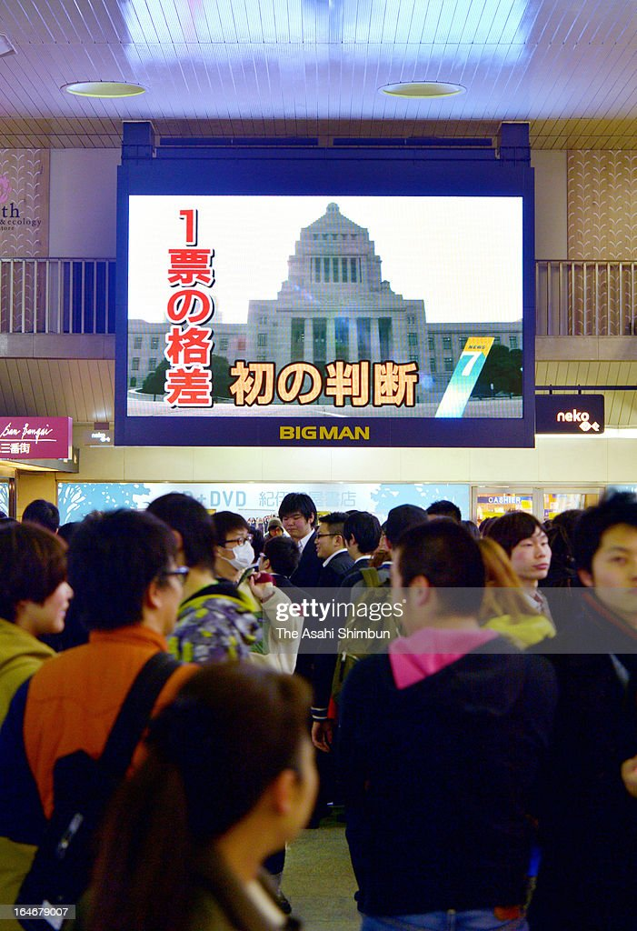 Commuters walk past the screen displaying the news Hiroshima court ruled the Dec 2012 election was invalid over vote disparity, on March 25, 2013 in Osaka, Japan. In a landmark decision, the Hiroshima High Court ruled on March 25 that the results of the Dec. 16 Lower House election in two constituencies were invalid due to the wide gap in the value of votes.