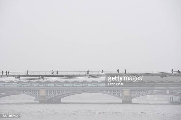 Commuters walk through the fog as they cross the Millennium Bridge on January 23 2017 in London United Kingdom Around 100 flights from airports...