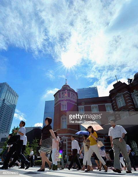Commuters walk under the blue sky after Typhoon Neoguri passed to the Pacific Ocean at Tokyo Station on July 11 2014 in Fukuoka Japan The Japan...