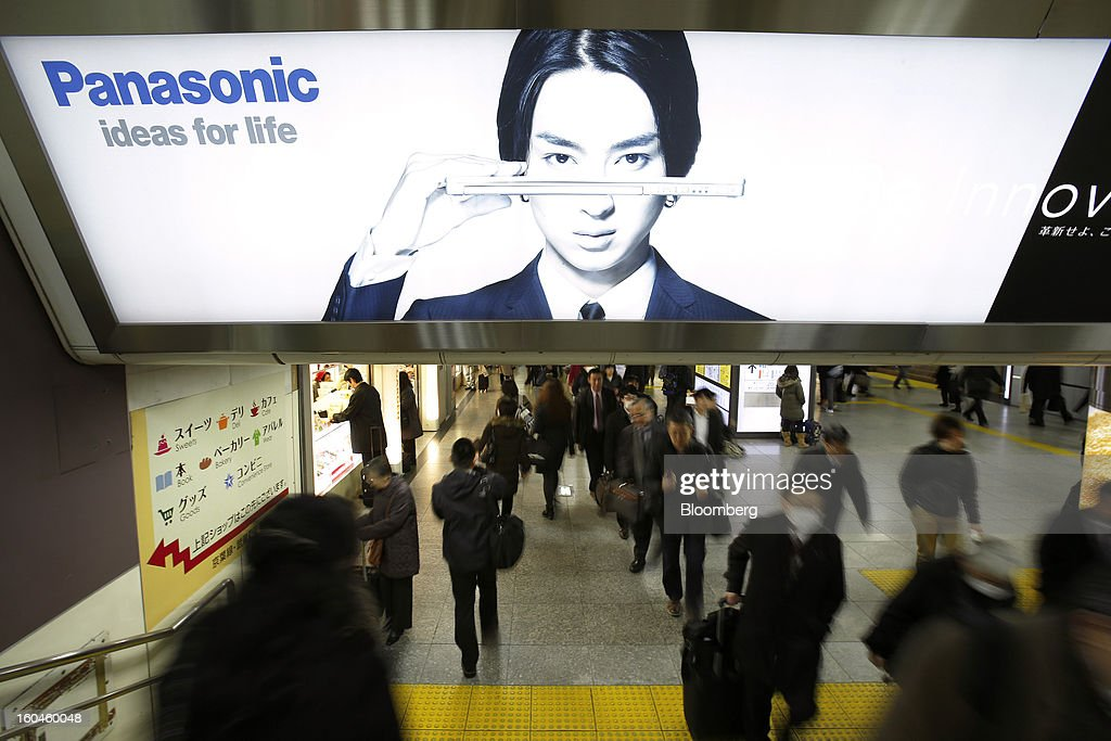 Commuters walk underneath an advertisement for Panasonic Corp. laptop computers displayed at a train station in Tokyo, Japan, on Friday, Feb. 1, 2013. Panasonic, Japan's second-biggest television maker, reported an unexpected third-quarter profit because of a weaker yen and restructuring efforts. Photographer: Kiyoshi Ota/Bloomberg via Getty Images