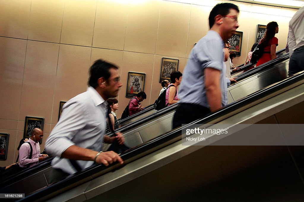 Commuters walk up an escalator inside the Raffles Place MRT station during rush hour at the central business district area on February 13, 2013 in Singapore. The government white paper revealed Singapore's population may increase 30% to over 6.9 million by 2030, with nearly half the population expected to be foreign-born. Many local residents are critising the plan concerned about the added strain on housing, transportation and healthcare and the diminishing identity of the Singaporean community.